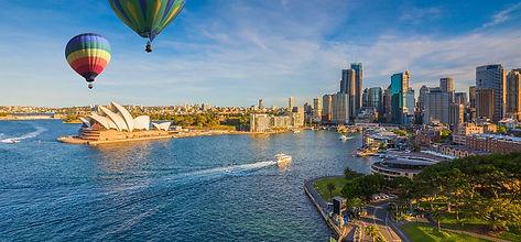 Hot air balloon over Sydney bay in eveni