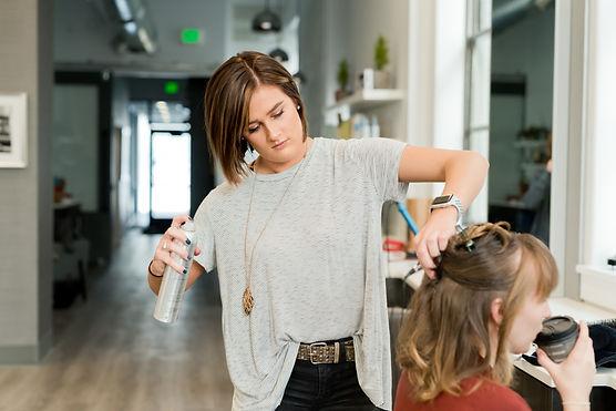 a hairdersser spays a clients hair
