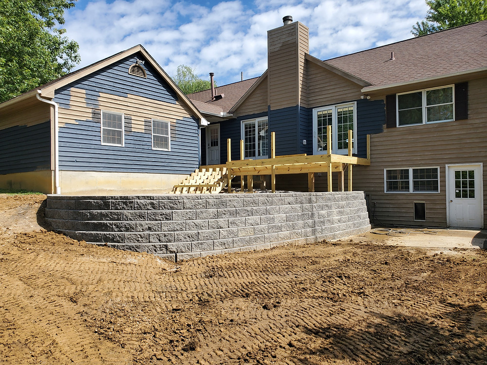 The wall is constructed from Allan Block Classic Collection in the Granite color.  The block retaining wall is holding up a paver patio and deck.