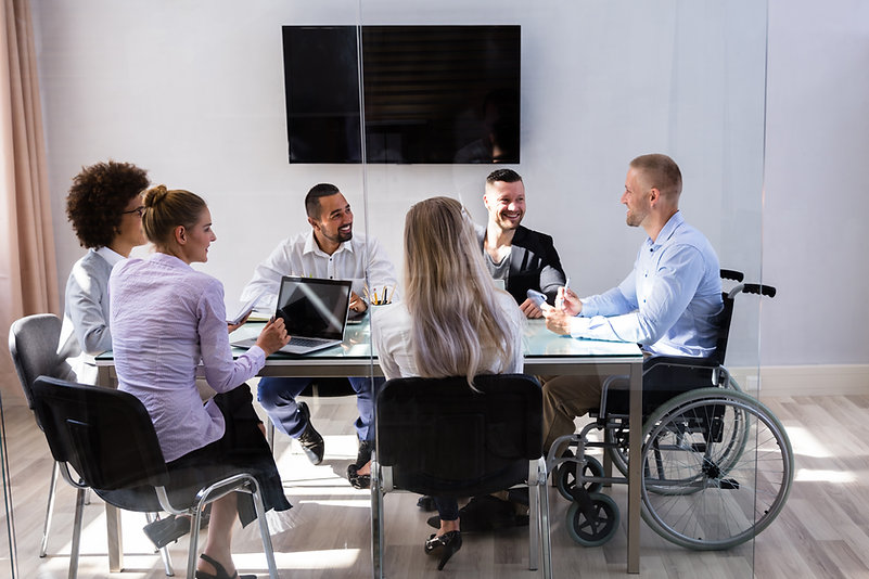 Five professionals seated around a conference table with man in a wheelchair discussing his claim.