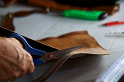 Cutting the leather by hand to turn into bespoke jewelry pieces