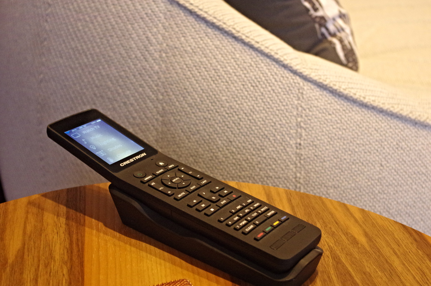 Crestron remote resting on end table