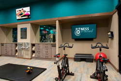 Blue exercise room with hanging TV