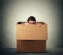 Young woman hiding in a carton box.jpg
