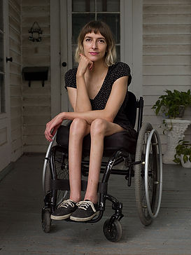 A lady in a blackdress sits in a wheelchair outside a white, wooden house.