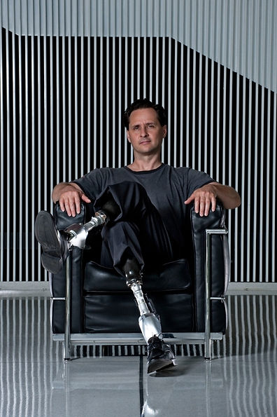 A man with prosthetic legs sits on a leather armchair in front of a black and white striped wall.