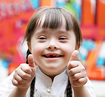 Mentally Disabled little girl with brown hair pulled back into braided pigtails holding both thumbs up smiling