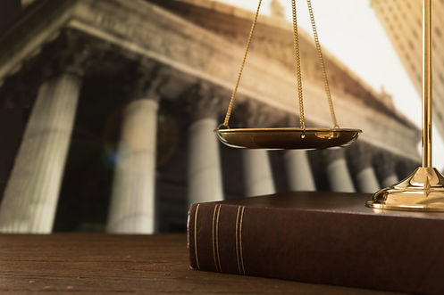 scales of justice on law books with cour