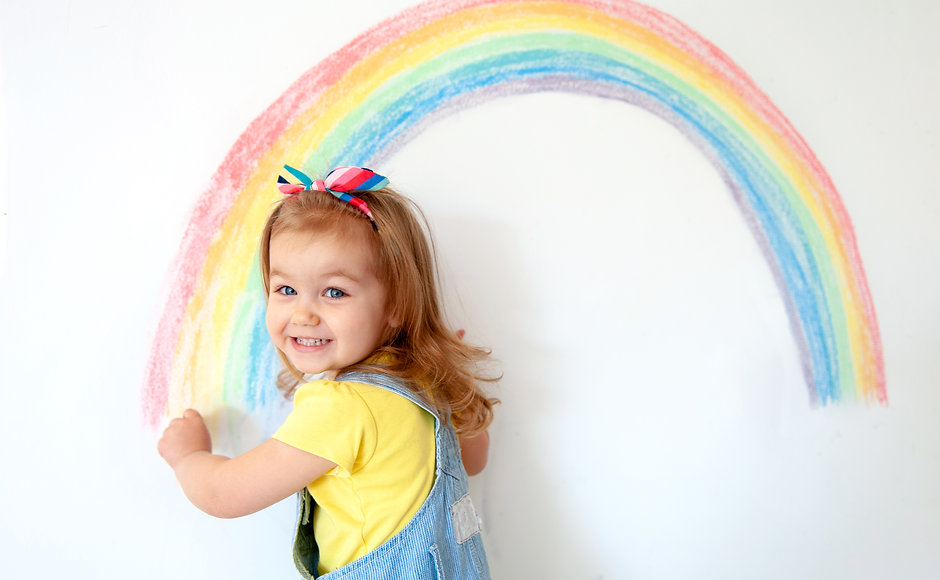 Super cute little girl drawing rainbow o