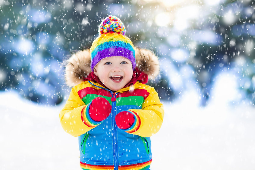 Child playing with snow in winter. Littl