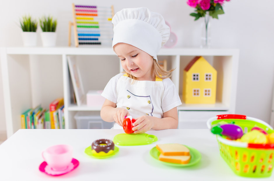Little blonde girl in white cook uniform