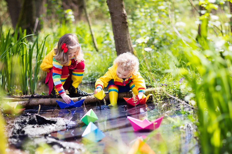 Children play with colorful paper boats