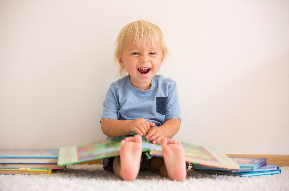 Sweet toddler boy, reading book at home,