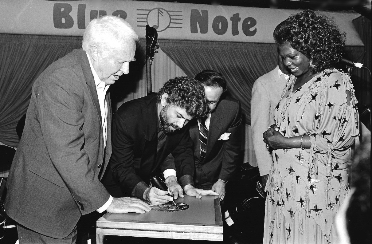 Monty Alexander signs Blue Note NYC table Herb Ellis and Ernestine Anderson watching