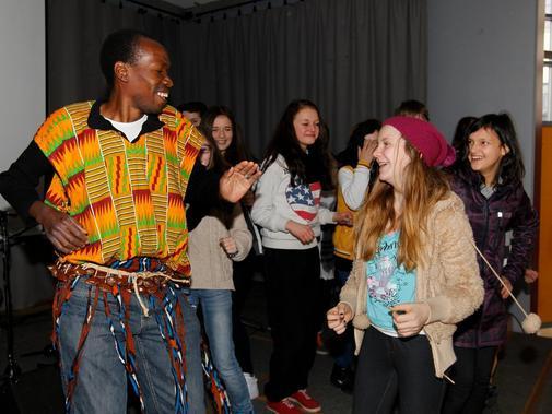 """Ausgelassen tanzen die jungen Leute mit einem Mitglied der """"Initiative Black&White e.V."""" zu afrikanischer Musik."""