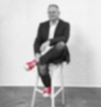 Black and white photo of man sitting on stool wth red shoes.