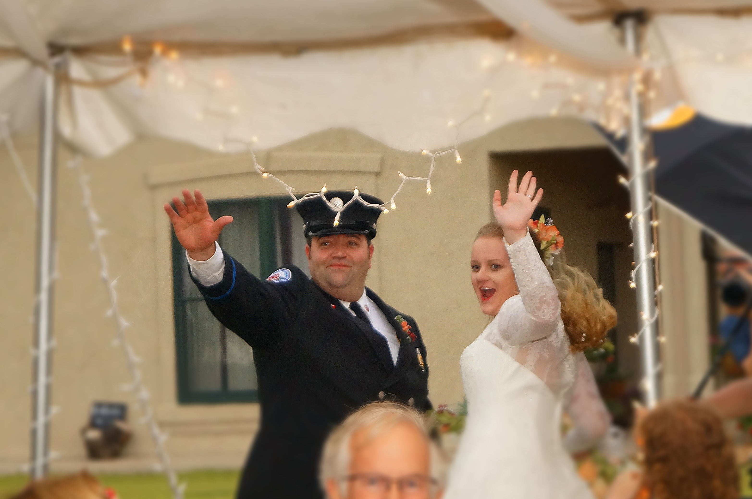 Newly married couple waving to crowd
