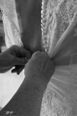Bride being buttoned up
