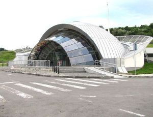 Photo of the entrance to Salina Turda, a small, shell-shaped building with elaborate glass panels and surrounded by a railing