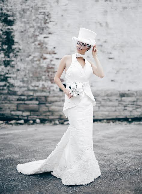 A woman wearing a white gown with a veil and tophat