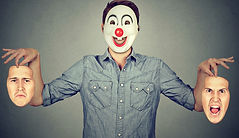 Man-in-happy-clown-mask-holding-two-face