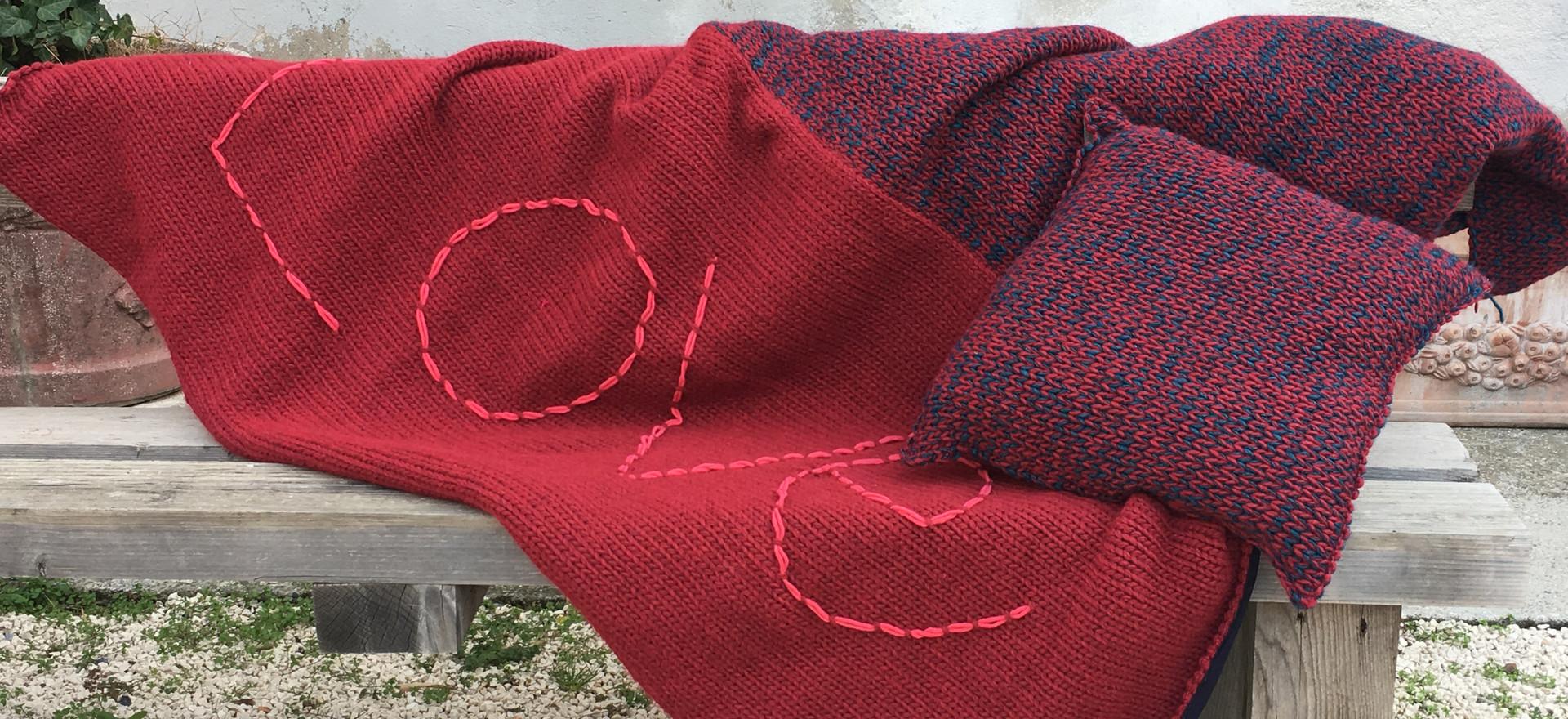 Cuscini e coperta maglia e tessuto. Ricami handmade
