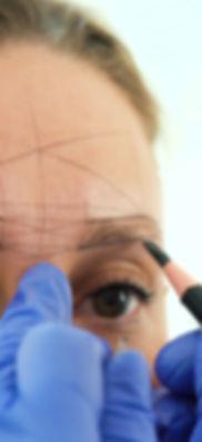 Cosmetologist preparing woman for eyebro