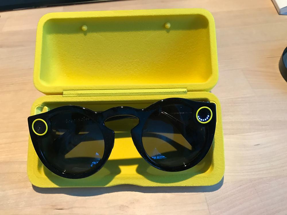 Brillen lader mens den ligger i futteralet (se hvit ring til høyre, indikerer batterinivå under lading)