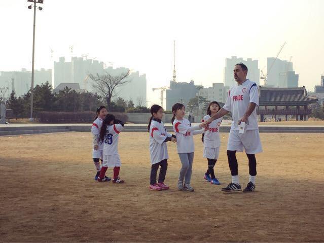 """Coach John"" with members of Pride Girls Soccer."