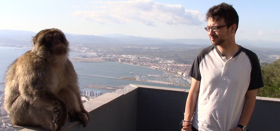 Dan on top of the Rock of Gibraltar, speaking with a monkey.