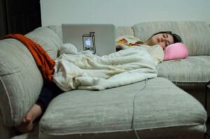 girl falling asleep with laptop on the couch