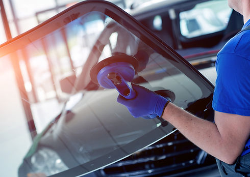 Automobile special workers replacing windscreen or windshield of a car in auto service sta