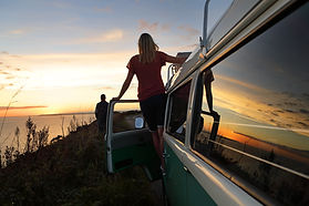 A woman watching the sunset from the door of her mini campervan