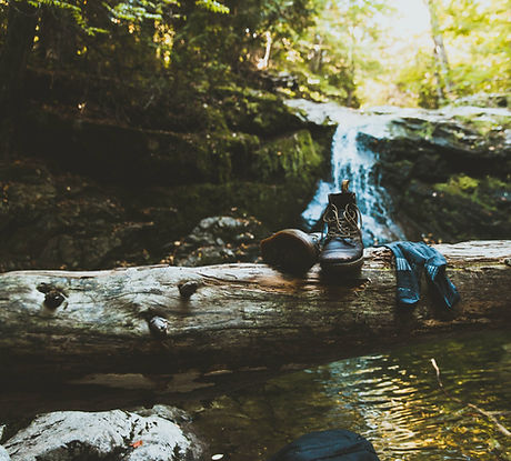 boots on a tree by a waterfall