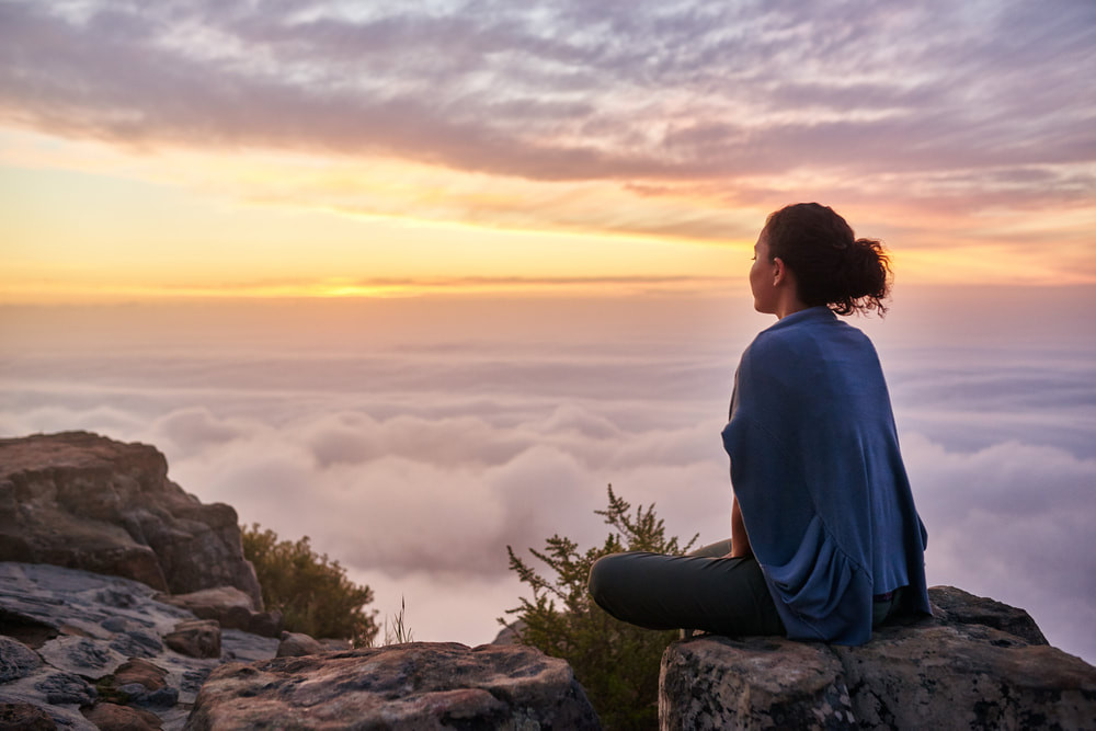 Woman meditating above clouds