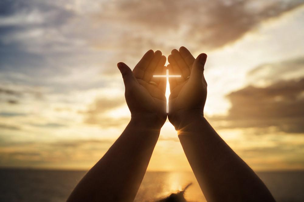 Hands held in prayer with cross