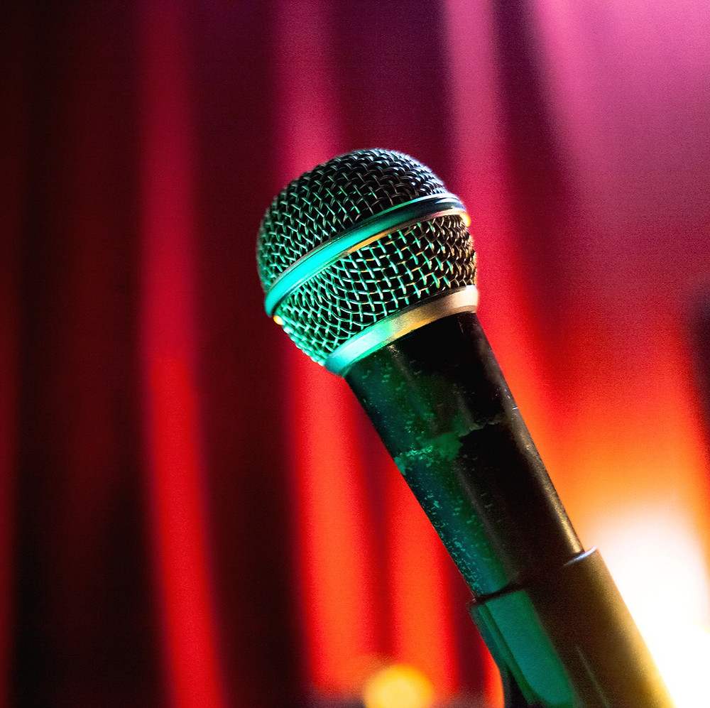 Microphone in front of a red curtain.