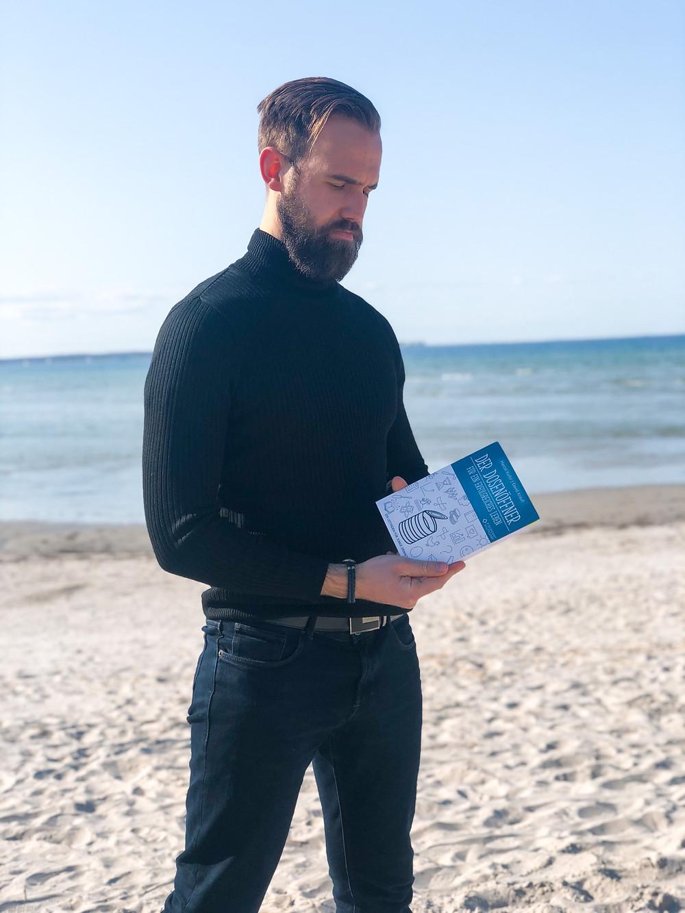 Jasper von bookbeaches mit dem Buch Der Dosenöffner an einem Strand in Kiel. Das Buch behandelt Themen wie Mindset, Geld, Umfeld und Fokus.