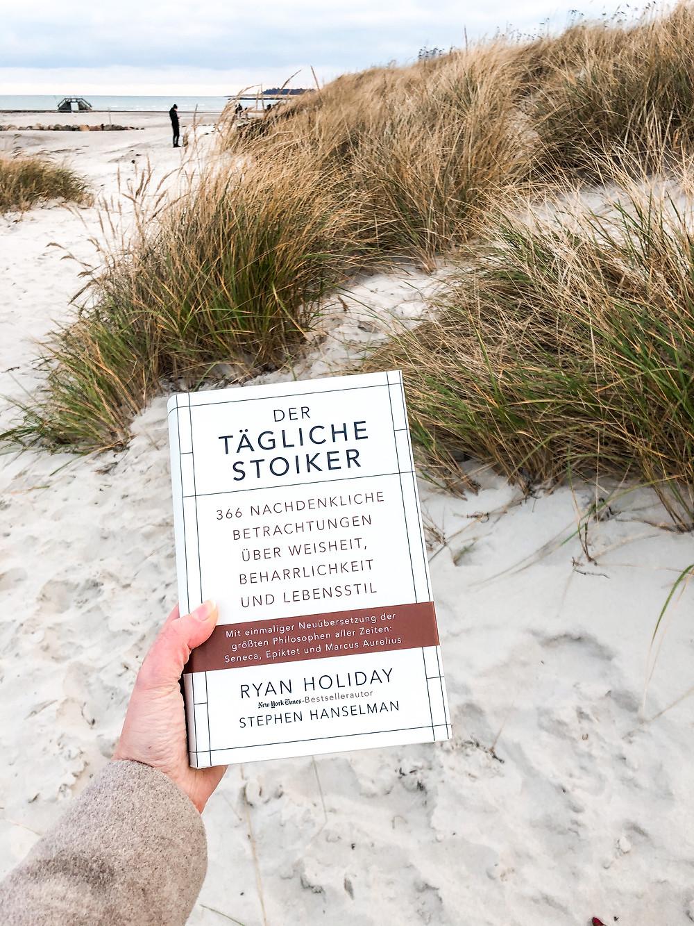 Die Rezension von dem Buch Der Tägliche Stoiker von Ryan Holiday von bookbeaches an einem Strand in Kiel.