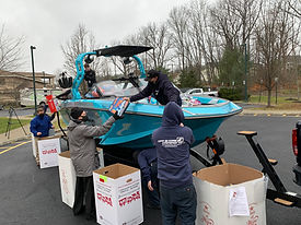 Lou Cecchini, Off Shore Marine, hands new toys to Bruce Tomlinson, Project Self-Sufficienc
