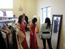 Teen girls try on prom dresses at the Sister to Sister Prom Shop.JPG