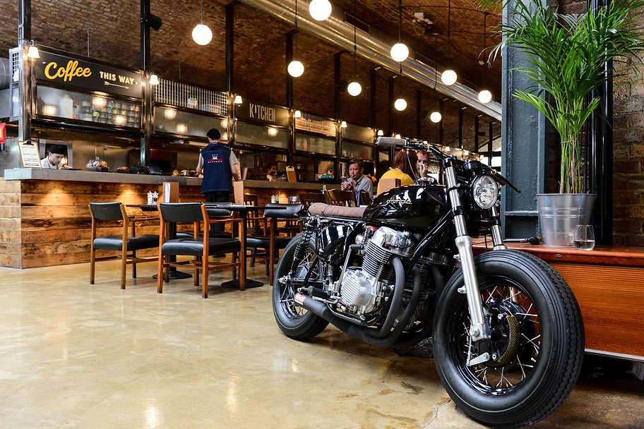 The Bike Shed Restaurant under the railway arches in Shoreditch London EC1, a black Honda CB motorcycle parked among the tables and chairs.