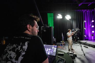Jordan Meher filming documentary on virtual stage in studio with camera op