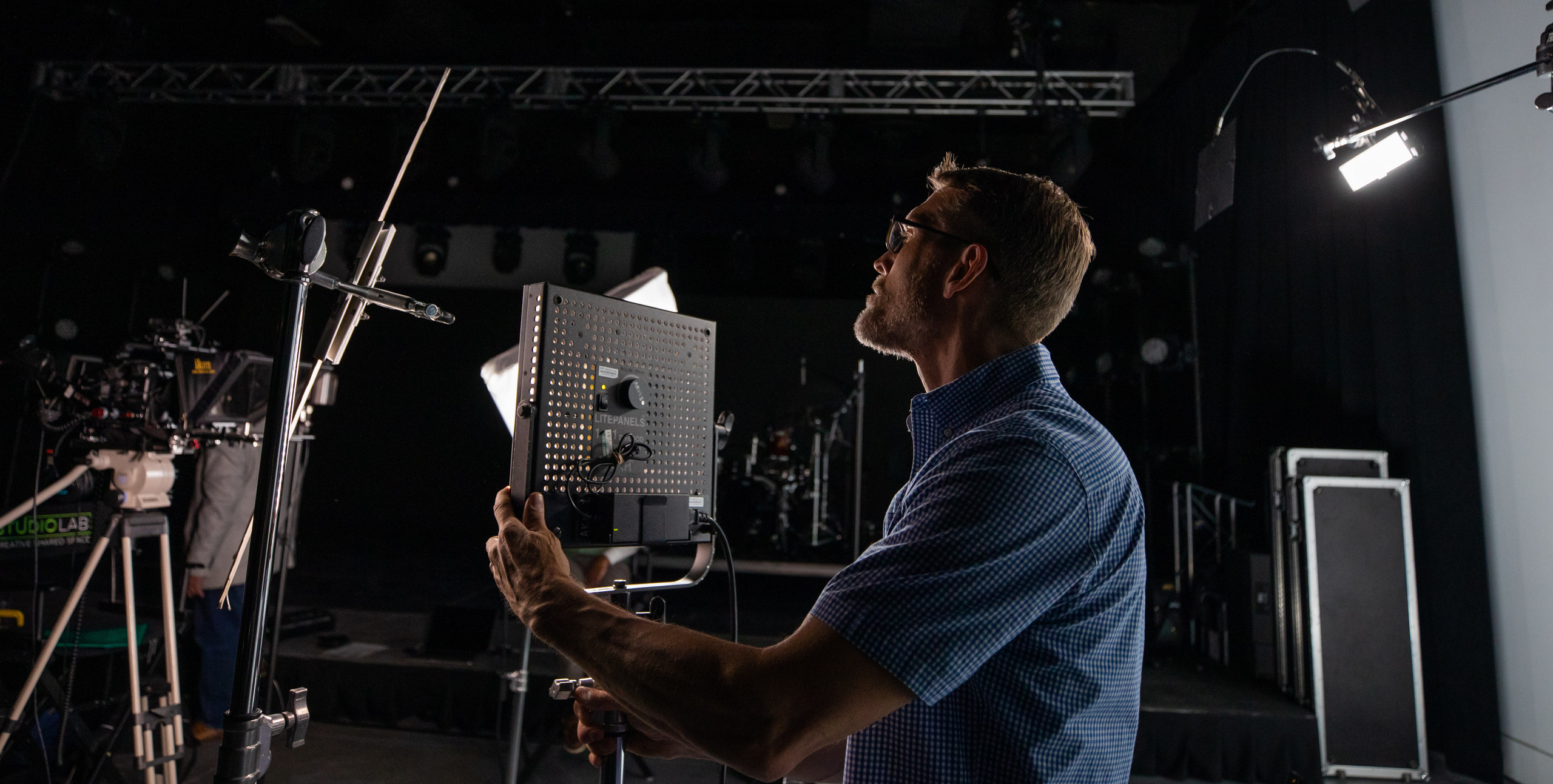 Kent Rich setting up lighting for video shoot in studio