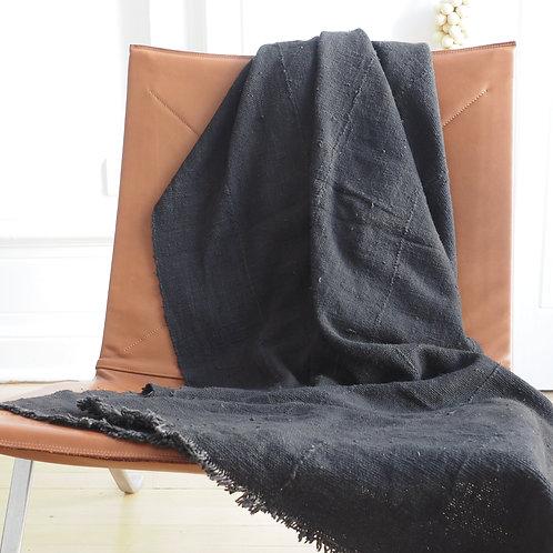 plaid-floatinghouse-ethnique-bogolan-noir-posé-sur-fauteuil-design