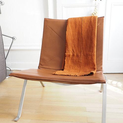 plaid-ethnique-chic-bogolan-terracotta-plié-sur-fauteuil-design