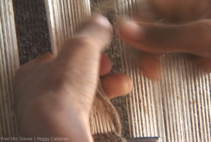 Close up hands weaving carpet