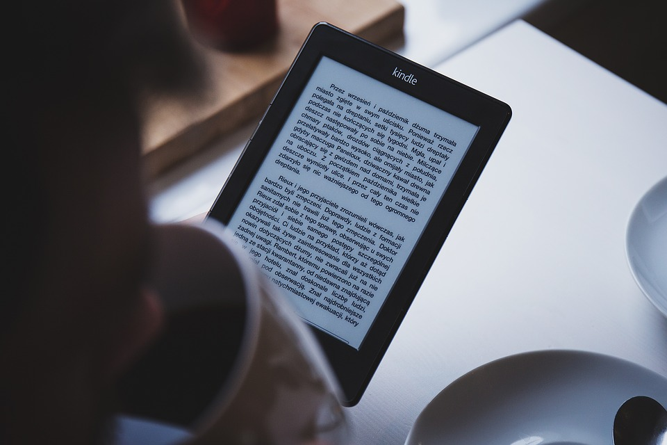 person sipping coffee while holding a Kindle