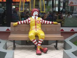 Ronald McDonald statue sitting on a bench.