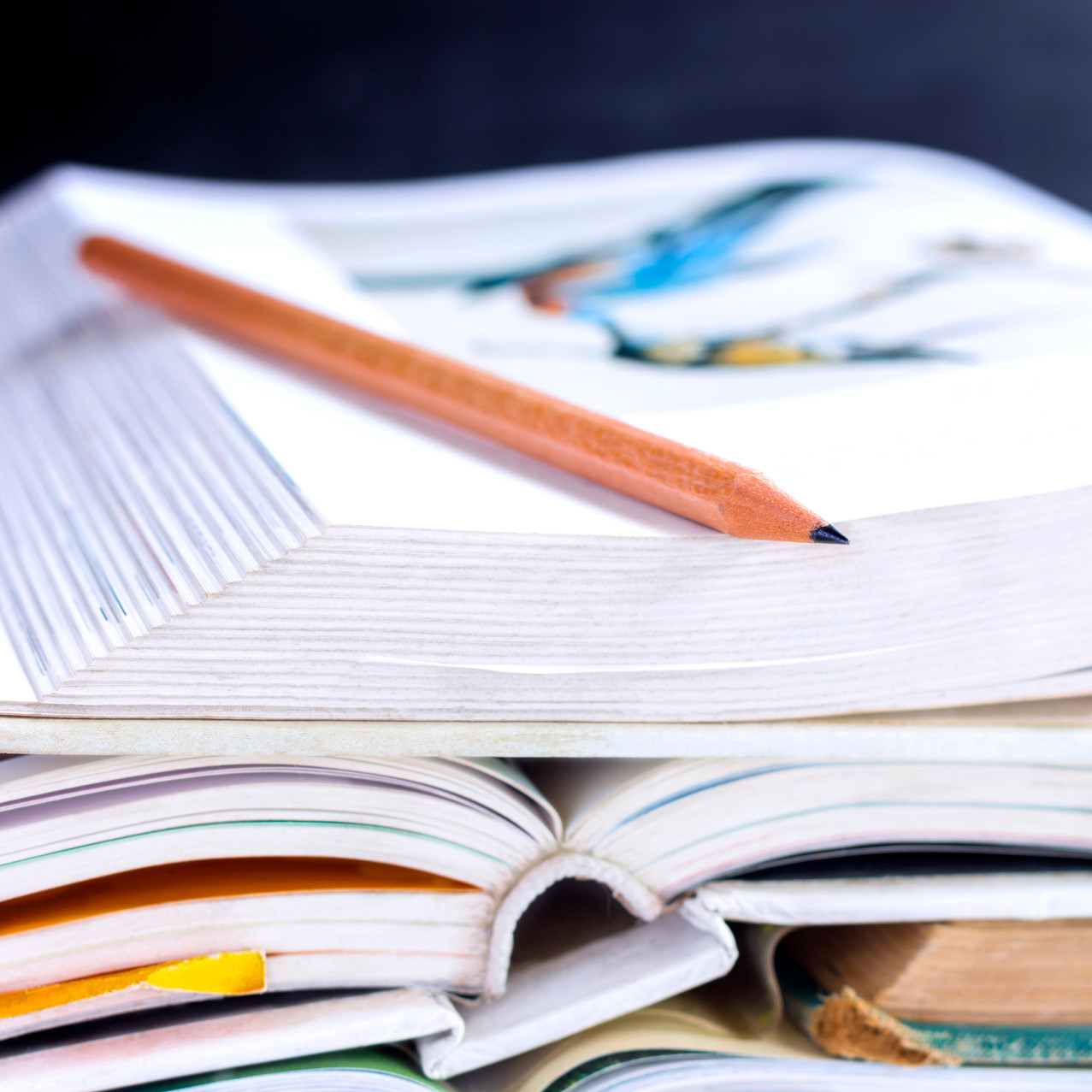 blurry photo of open textbook stacked on top of other textbooks with a pencil